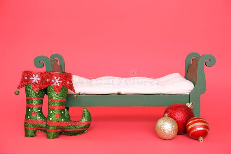 Digitalfotografie-Hintergrund des grünen Weinlese-Weihnachtsbaby-Betts lokalisiert auf Rot lizenzfreie stockbilder