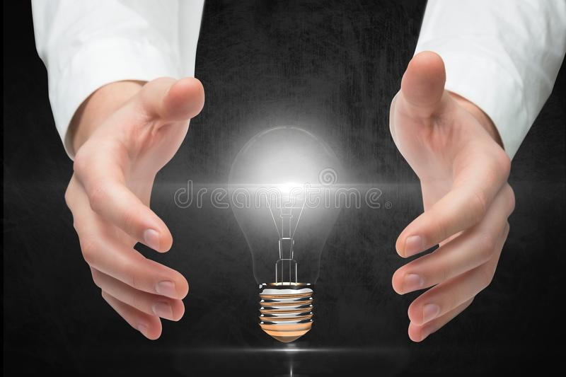 Digitally generated image of hand covering electric bulb against gray background stock images