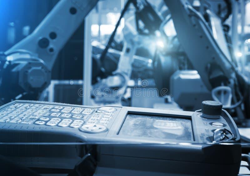Digitalregler For Robot in der Fabrik vor dem hintergrund der unscharfen gelben Industrieroboter lizenzfreies stockfoto
