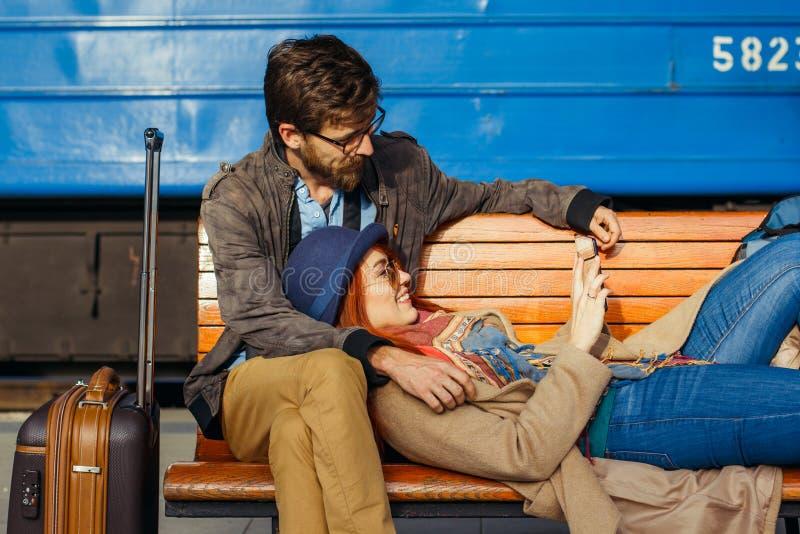 Digitaltechnik und Reisen Junge liebevolle Paare im Hippie tragen mit Tablet-Computer beim Sitzen im Bahnstation wai lizenzfreie stockfotos