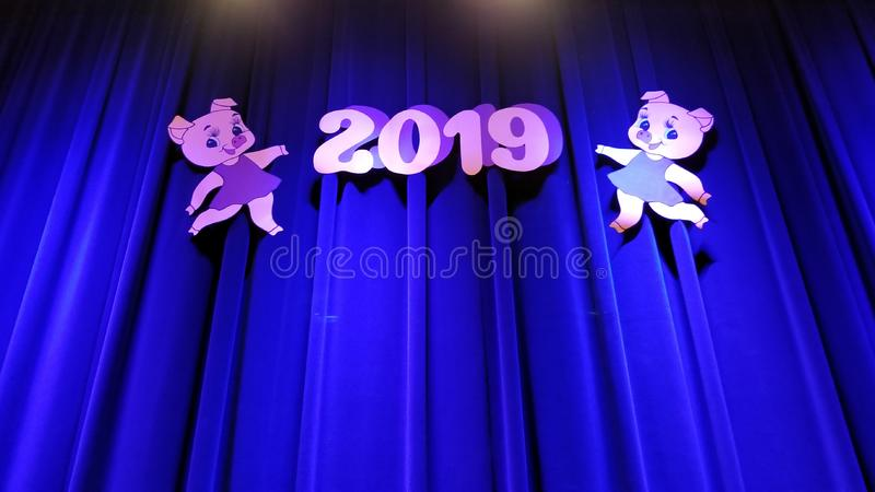 Digits 2019 and pink pig images on the sides on the blue curtains illuminated from above.  stock photos