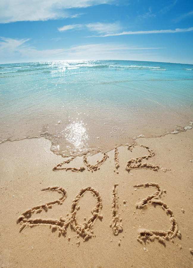 Digits on the sand. Digits 2012 and 2013 on the sand seashore - concept of new year stock images