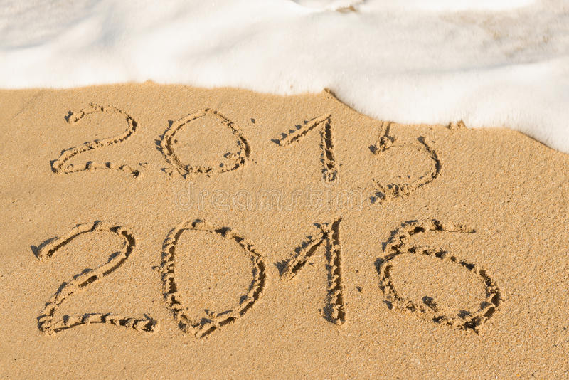 Digits on the sand. Digits 2015 and 2016 on the sand seashore - concept of new year and passing time stock photography