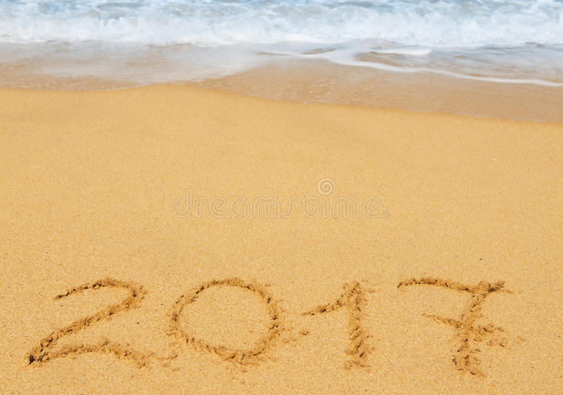 Digits 2017 on the sand. Seashore - concept of new year and passing of time royalty free stock image