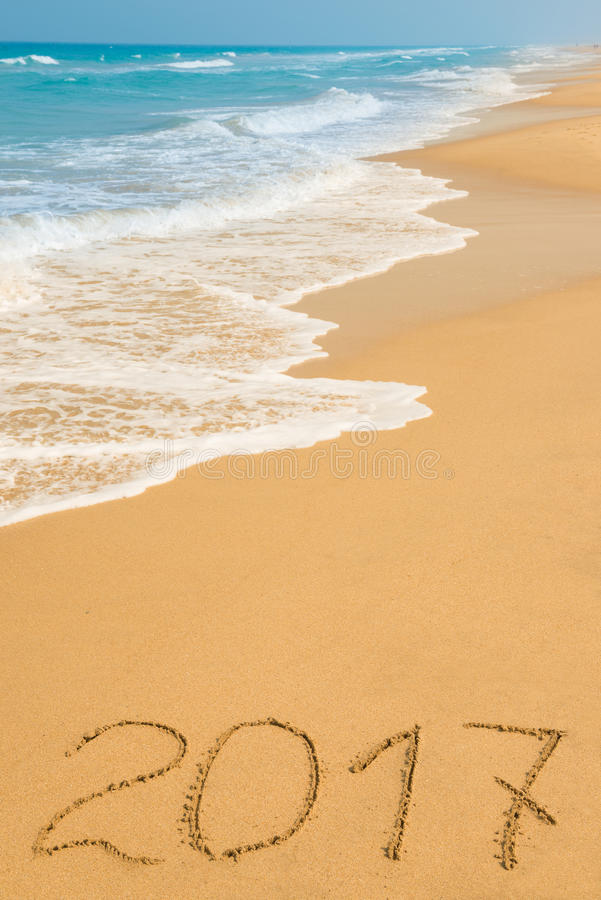 Digits 2017 on the sand. Seashore - concept of new year and passing of time stock images