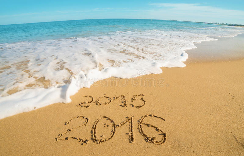 Digits on the sand. Digits 2015 and 2016 on the sand seashore - concept of new year and passing time.Wide angle royalty free stock images