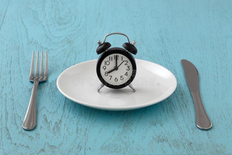 Digiuno intermittente con l'orologio sul piatto bianco fotografie stock libere da diritti