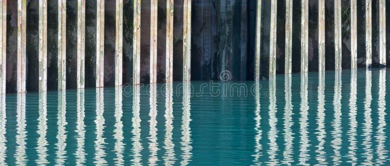 Digue rouillée se reflétant dans l'eau photos libres de droits