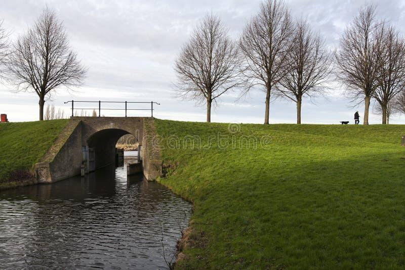Dijk met historische brug en sluis stock afbeeldingen