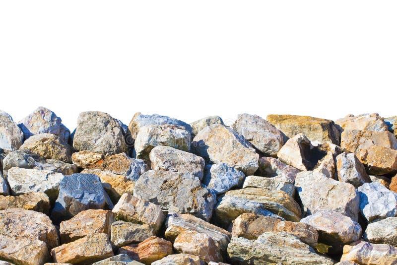 Dijkmuur met grote die steenblokken langs de kusten voor bescherming tegen overzeese onweren worden gebruikt - beeld op witte ach royalty-vrije stock foto's