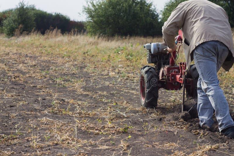 DIKANKA UKRAINA, WRZESIEŃ, - 30, 2015: Kraju rolnik orze jego ogród za z ogrodowym ciągnikiem zdjęcie stock