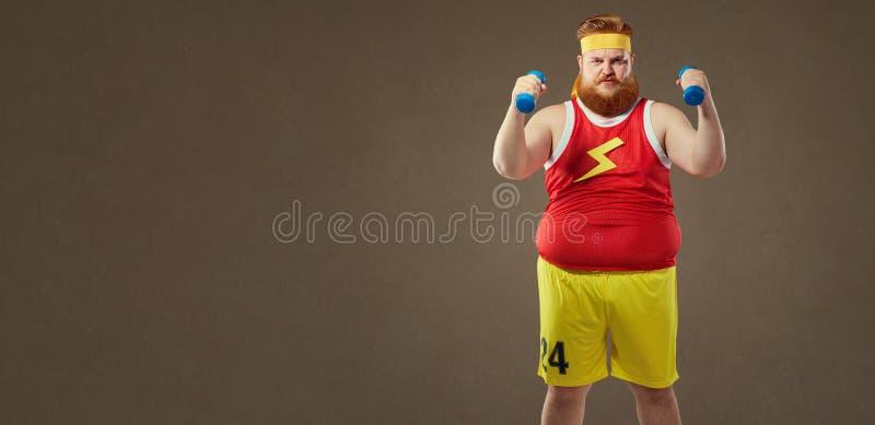 Dikke grappige kerel in sportkleding met kleine domoren stock foto