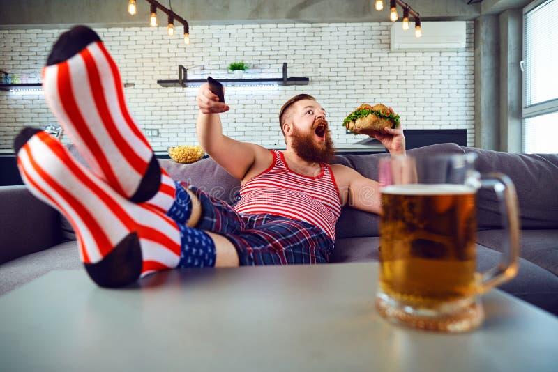 Dikke grappige mens die een hamburgerzitting op de laag eten royalty-vrije stock fotografie