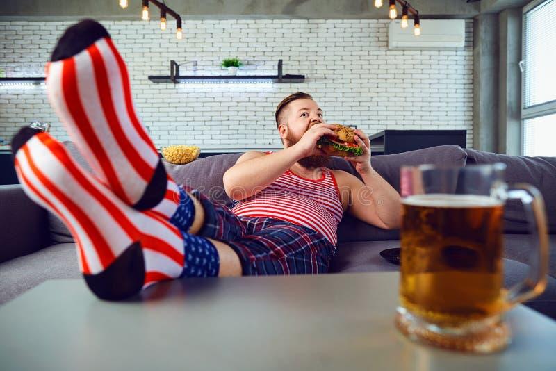 Dikke grappige mens die een hamburgerzitting op de laag eten stock foto