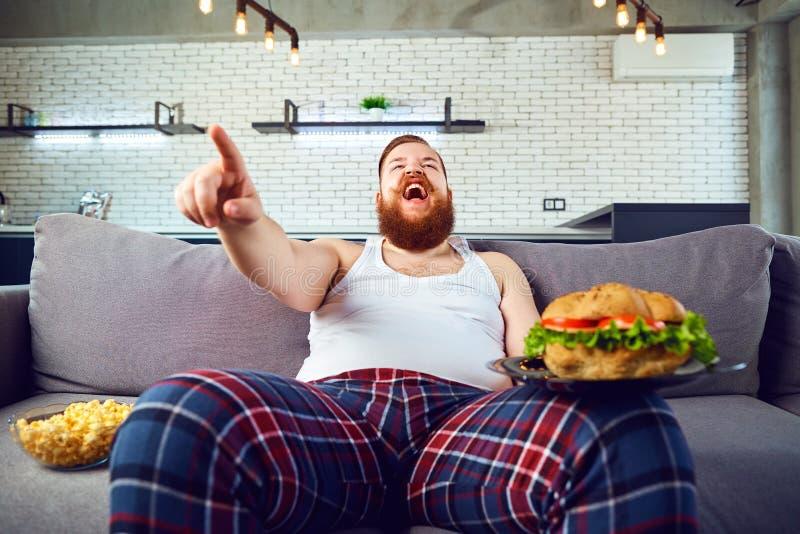 Dikke grappige mens met een hamburgerzitting op de laag royalty-vrije stock foto