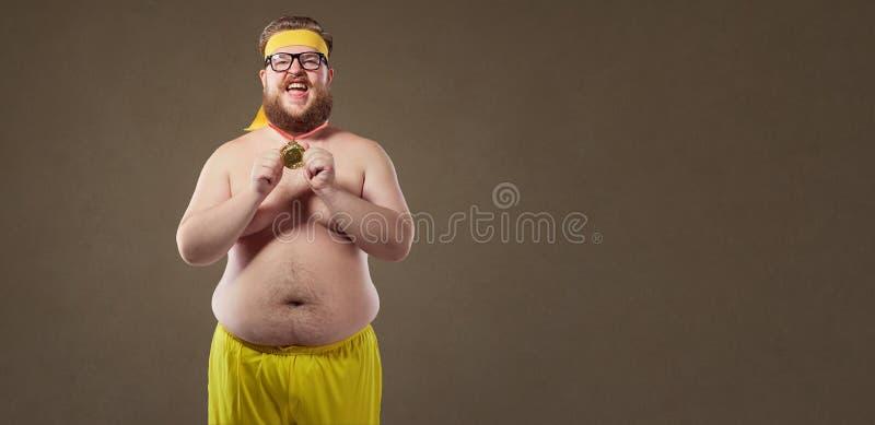 Dikke grappige mens met een medaille in zijn handen stock afbeeldingen