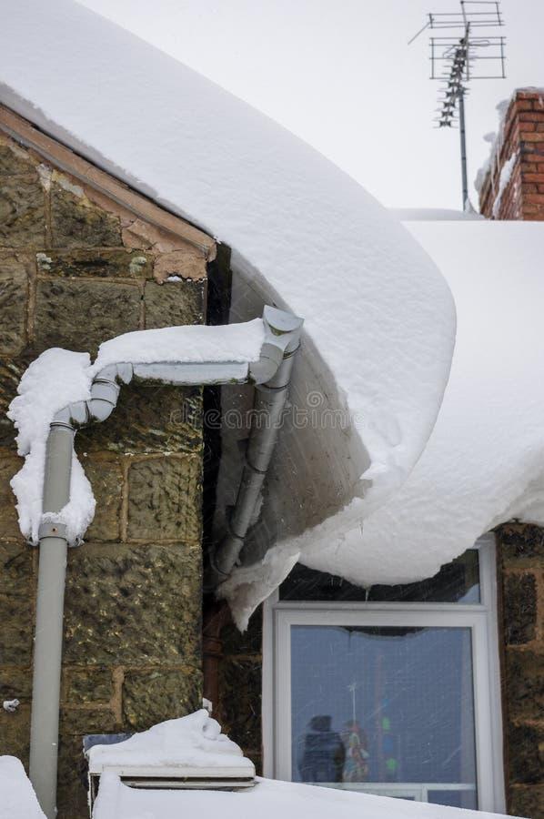 Dikke sneeuw die schade aan huis dak en het guttering veroorzaken stock foto