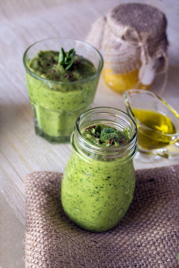Dikke voedzame smoothies, die omvatten: avocado, appel, banaan, spinazie, jus d'orange, honing, lijnzaad, munt en olijfolie stock foto's
