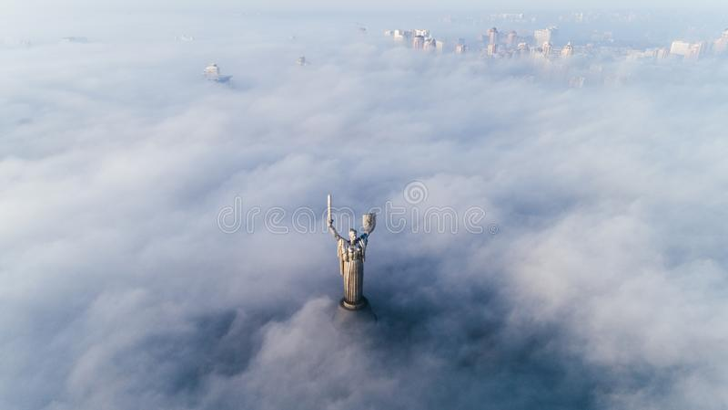 Dikke wolken van de herfstmist en het monument die van het Vaderland uit hen plakken stock fotografie