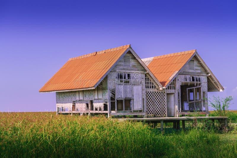 Dilapidé d'une maison jumelle emblématique de Talaynoi au ciel bleu, pont Chaloem Phrakiat, Phattalung en Thaïlande images stock