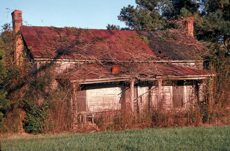 Dilapidated and abandoned home. Image shows a dilapidated and abandoned home slowly but surely being absorbed back into the environment. This would be a fixer royalty free stock images