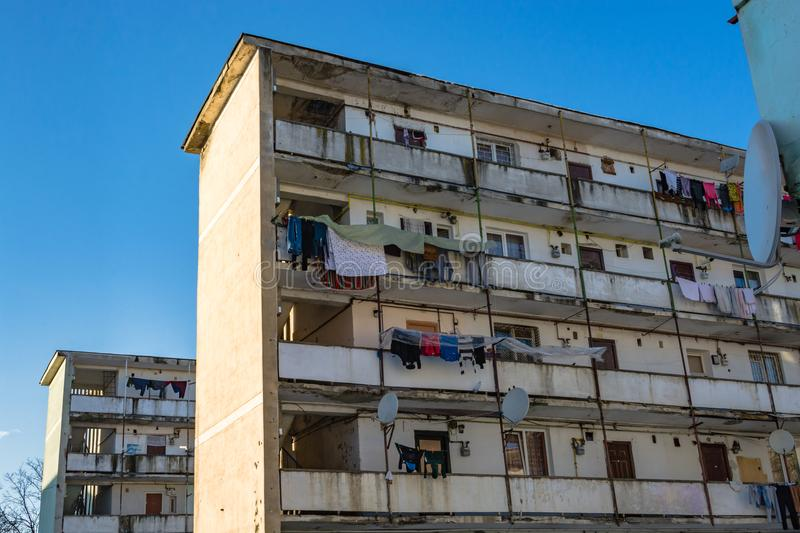 Dilapidated block of flats. Dirty dilapidated block of flats with clothes hanging to dry on windows and balconies. Inspires poverty, indigence and misery stock photos