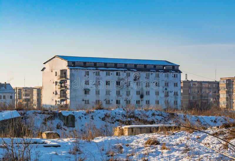 Dilapidated block of flats. Dirty dilapidated block of flats on a snow covered field. Inspires poverty, indigence and misery stock photos