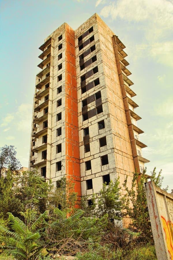 Dilapidated bouw met meerdere verdiepingen die met installaties wordt overwoekerd royalty-vrije stock afbeelding