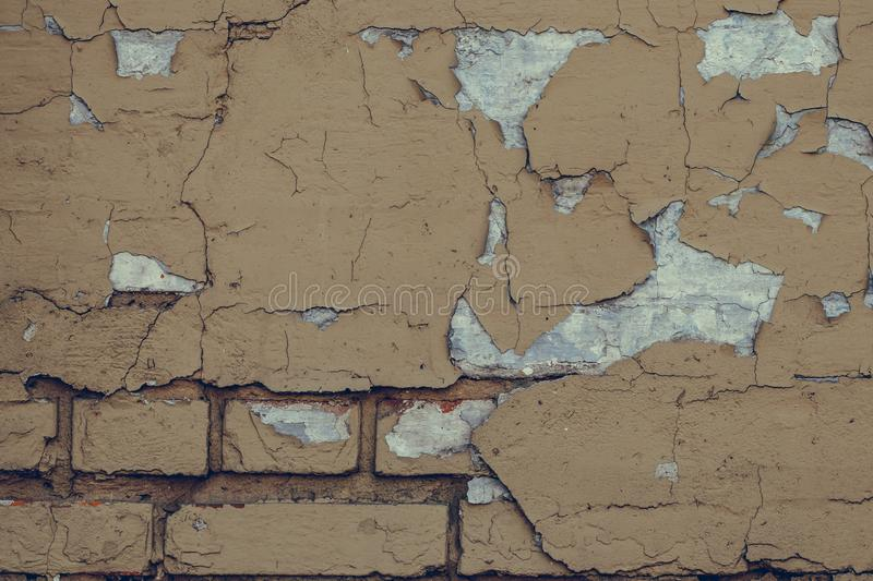 Dilapidated brick wall background. Grunge texture wall with peeling paint. Cracked light brown wall texture background. Vintage ho royalty free stock image