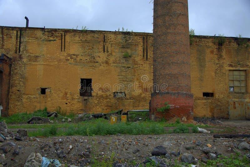 Dilapidated en verlaten baksteen bouw van een oude fabriek met een schoorsteen Landschap royalty-vrije stock foto