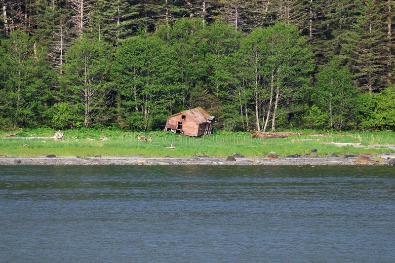 Fixer upper house on shore in Alaska. Dilapidated house on shore in Alaska. Trees in background and ocean inlet in foreground royalty free stock photos