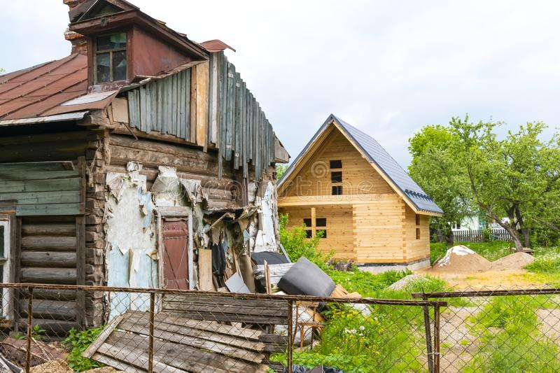 Dilapidated house and house under construction stock photos