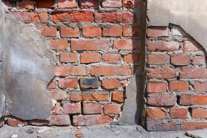 A dilapidated red brick wall on which plaster fell off fragment. Collapsing brick wall of the town house, built of red brick with peeling plaster fragment stock image