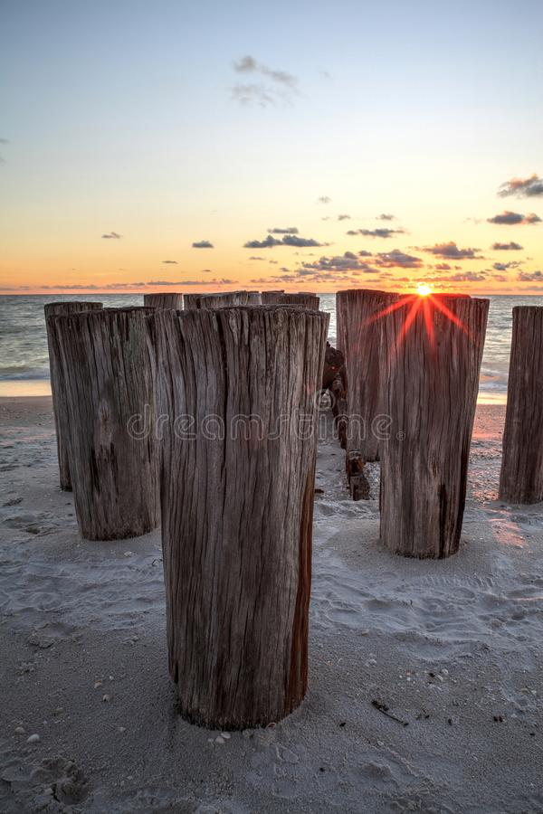 Dilapidated ruins of a pier on Port Royal Beach at sunset. In Naples, Florida stock images