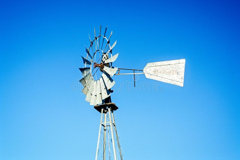 Old west windmill. Dilapidated western water wheel, iconic symbol of the Old West, with pure blue sky stock photo