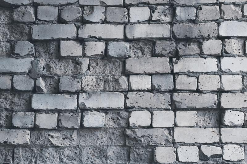 Dilapidated white brick wall, grunge background. Gray brick wall pattern, weathered texture. Grey stone concrete wall. Old cracked royalty free stock photography