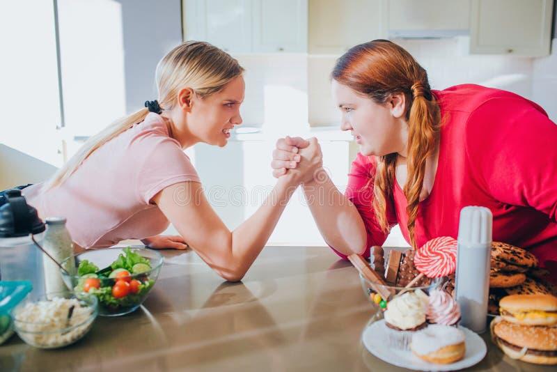 dilemma Para perder o peso ou não Aptidão contra a loção do corpo A jovem mulher delgada atlética afirma em armwresling com gordu fotos de stock royalty free