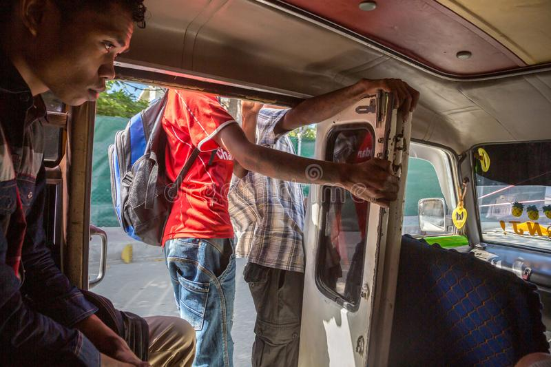 Teenage boy and other men inside a mikrolet bus driving with an open door, East Timor. Micro let minibus dangerous ride in capital royalty free stock photography