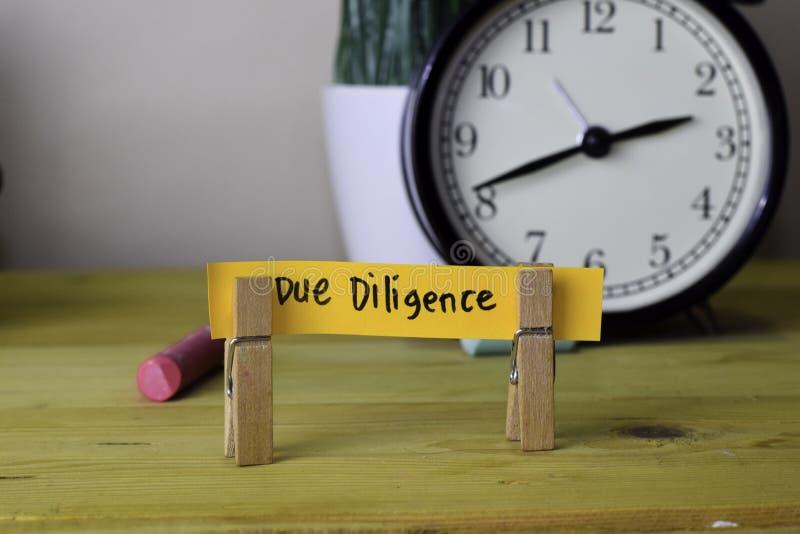 Dilig?ncia devida Escrita em notas pegajosas em Pegs de roupa na mesa de escritório de madeira fotografia de stock royalty free