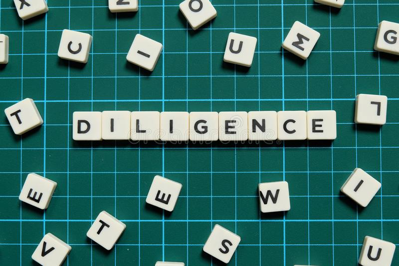 Diligence word made of square letter word on green square mat background. Diligence word made of square letter word on green square mat background royalty free stock photos