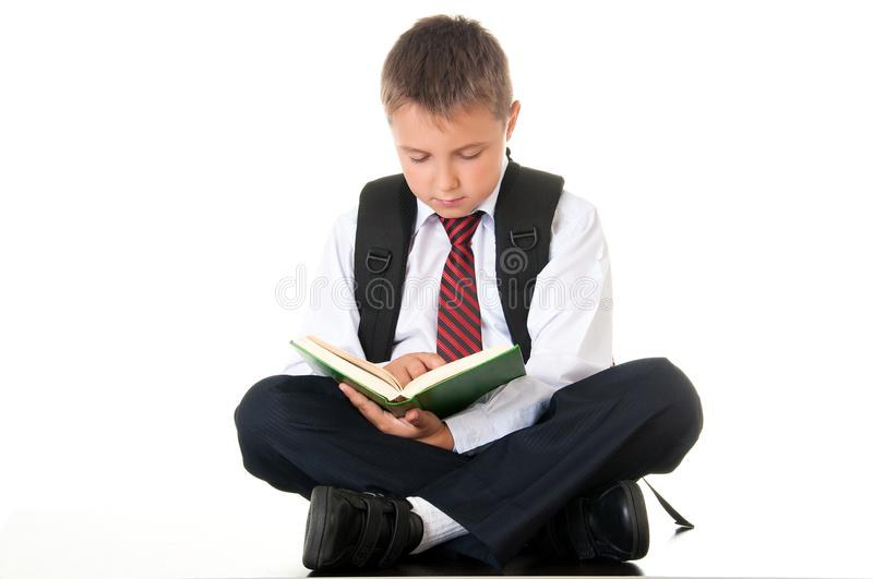 A diligent boy reads a book and prepares for exams and tests. Schoolboy teenager dressed in a school uniform. Isolated white royalty free stock image