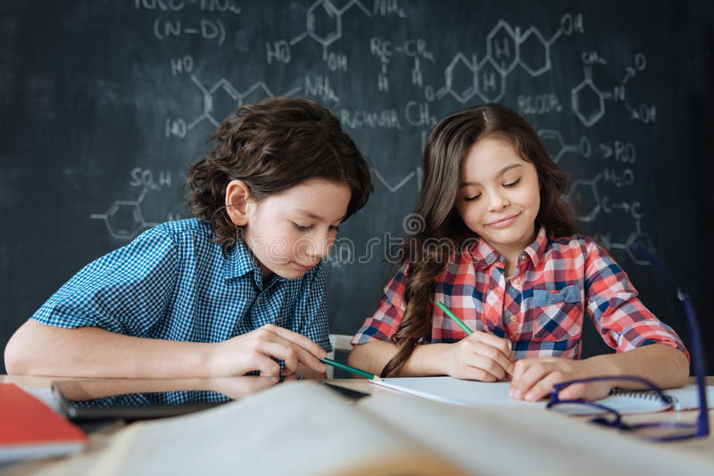 Diligent little pupils enjoying class at school royalty free stock photos