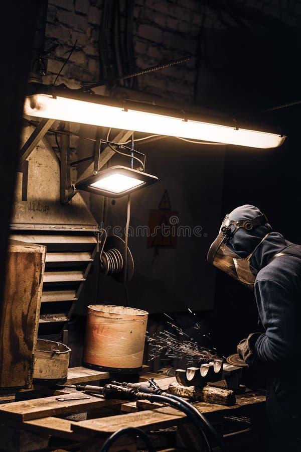 Diligent man trabalha com metal na oficina foto de stock