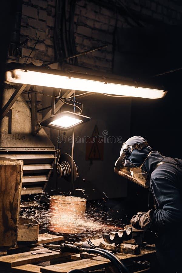Diligent man trabalha com metal na oficina imagens de stock royalty free