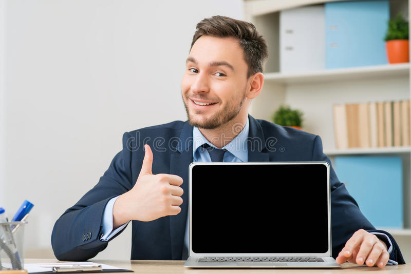 Diligent office worker pointing out his laptop. Works great. Pleasant cheerful upbeat office worker showing his laptop and thumbing up while sitting at the table stock image