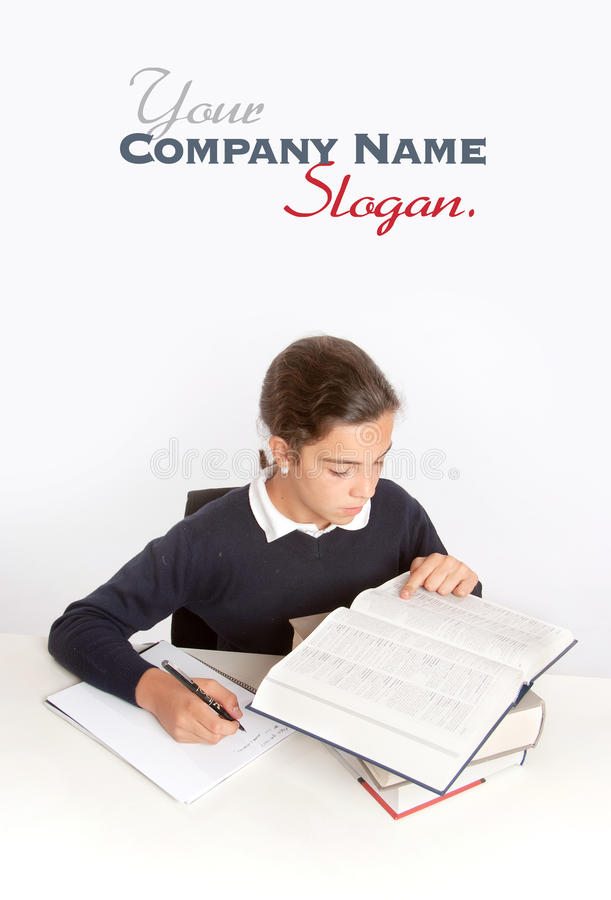 Diligent schoolgirl. Schoolgirl consulting a dictionary while writing an essay stock photography