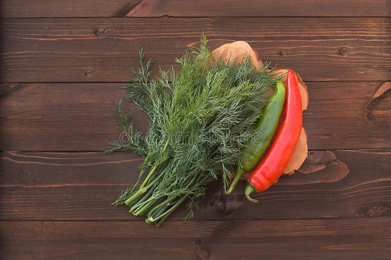 Dill green and hot pepper red and green on a wooden background w. Dill green and hot pepper red and green fresh fragrant rustic farmhouse on a wooden background stock photos