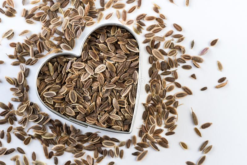 Dill Seeds in a Heart Shape. Top view of whole dill seeds in a heart shape stock photos