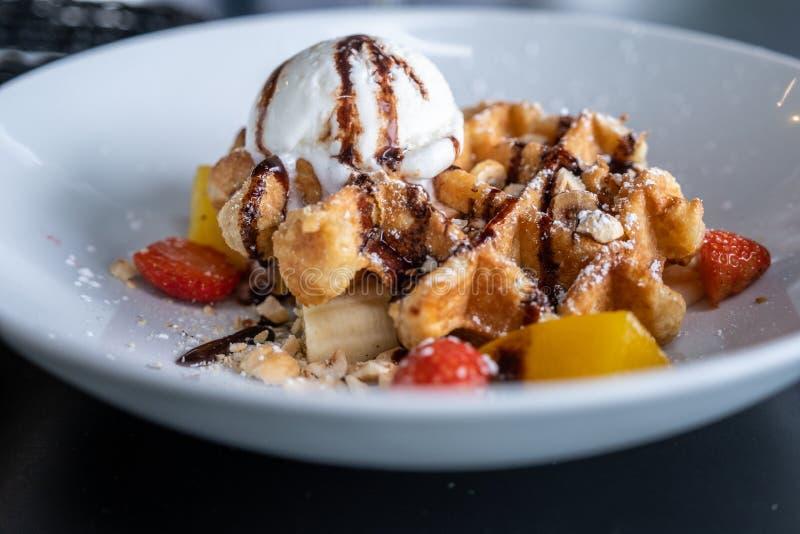 Dillandear med choklad täckte glass och som dekorerade med frukt på en platta på tabellen royaltyfria foton