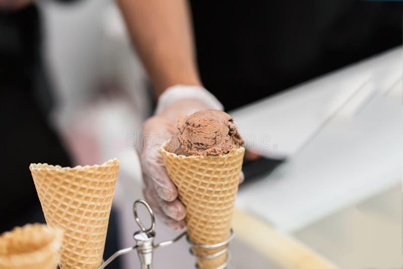 Dillandekotte, horn med bollen av choklad, mjuk glass för kaffe och hand av säljaren Läcker kyla del för gyckel royaltyfri fotografi